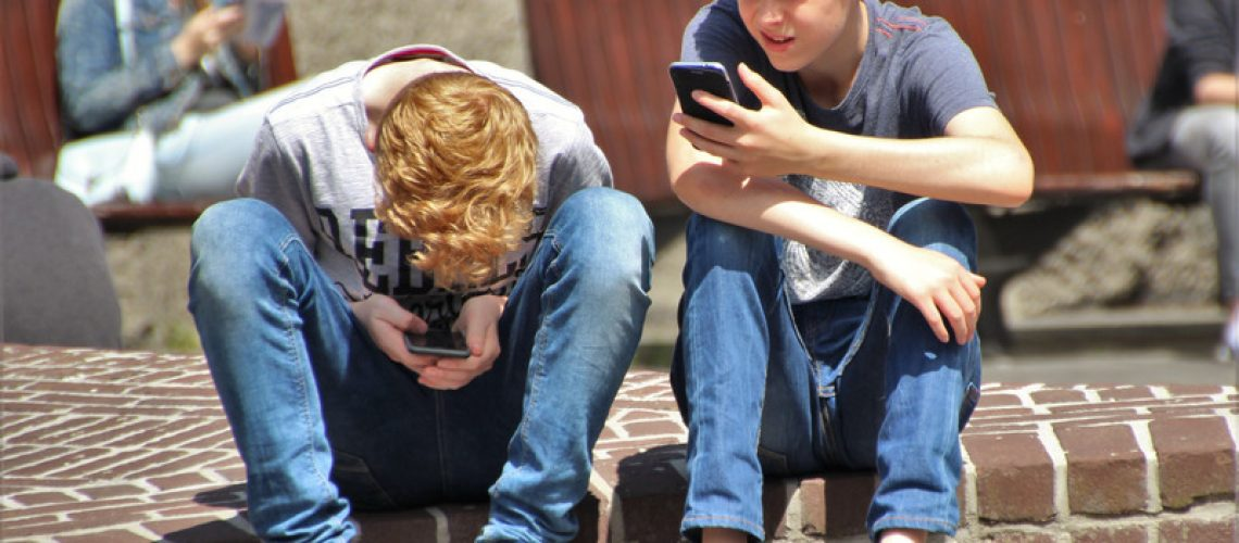 boy-sitting-on-brown-floor-while-using-their-smartphone-near-woman-siiting-on-bench-using-smartphone-during-daytime